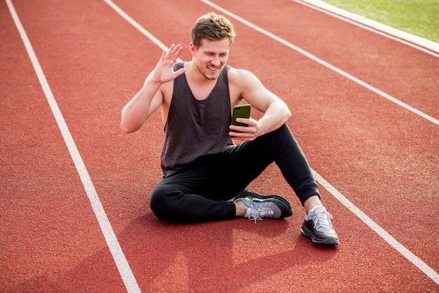 Giovane atleta maschio sorridente che si siede sulla pista di corsa rossa che ondeggia le sue mani mentre facendo videochiamata Foto Gratuite