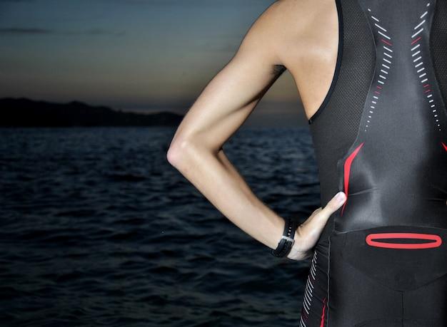 Giovane atleta triathlon di fronte a un alba sul mare Foto Premium