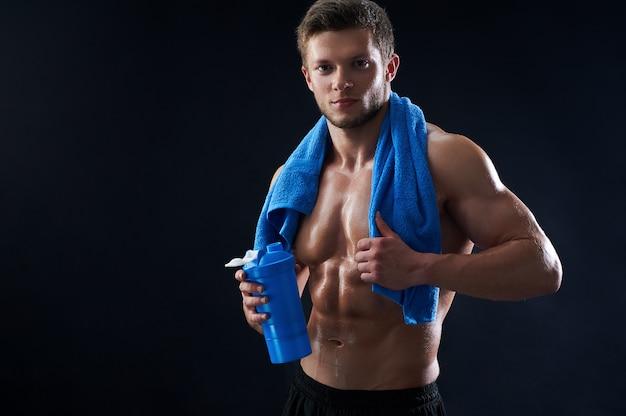 Giovane atletico senza camicia con un asciugamano e una bottiglia di acqua dopo Foto Gratuite