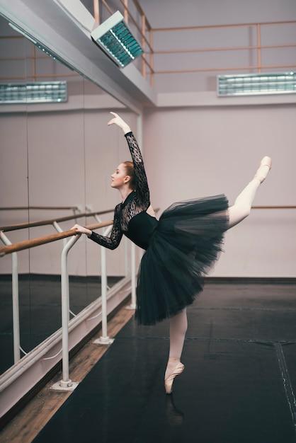 Giovane ballerina di danza classica praticando nello studio di danza Foto Gratuite