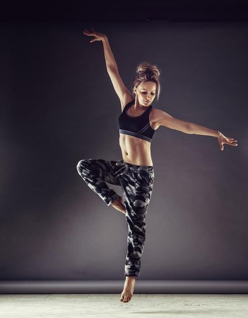 Giovane ballerina donna sottile in abbigliamento sportivo salto in alto sul fondo della parete Foto Premium