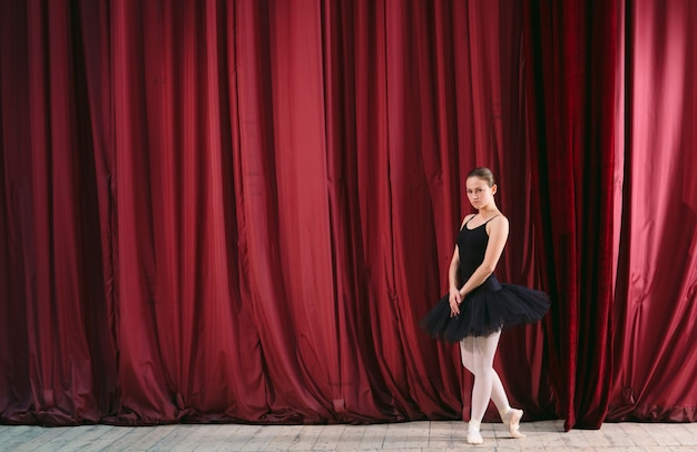 Giovane ballerina in abito nero si allena dietro le quinte. Foto Premium