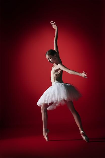 Giovane ballerino di balletto femminile grazioso o ballerina classica che balla allo studio rosso. Foto Gratuite