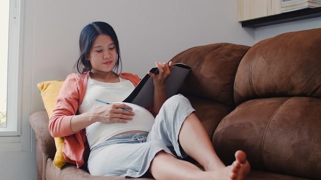 Giovane bambino asiatico del disegno della donna incinta in pancia in taccuino. mamma che ritiene felice sorridente positivo e pacifico mentre abbi cura del bambino che si trova sul sofà in salone a casa. Foto Gratuite