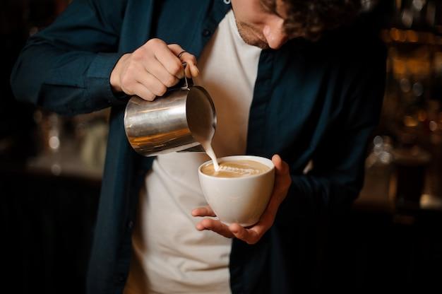 Giovane barista che versa un po 'di latte in una tazza di caffè Foto Premium