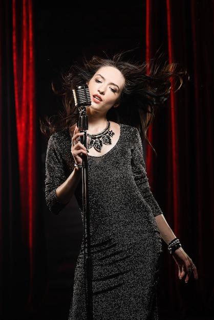 Giovane bella cantante in abito nero con capelli fluenti canta nel microfono Foto Premium