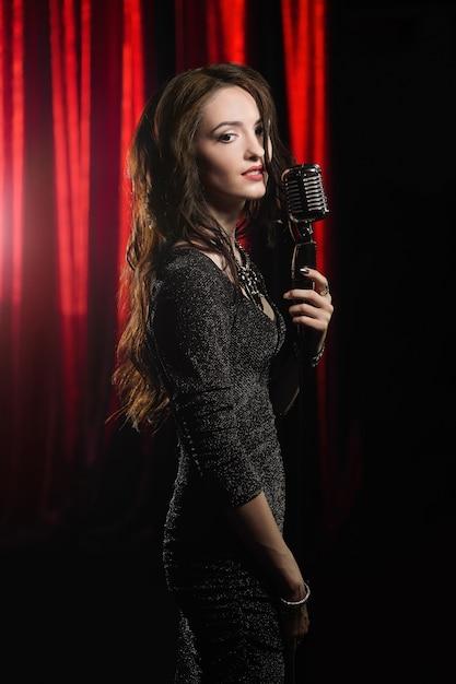 Giovane bella cantante in abito nero in posa con il microfono Foto Premium