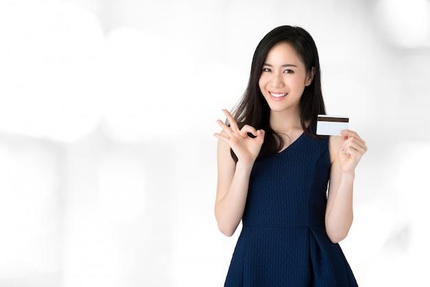 Giovane bella donna asiatica sorridente che mostra la carta di credito con il gesto di okey Foto Premium
