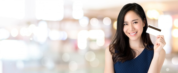 Giovane bella donna asiatica sorridente che presenta carta di credito in mano Foto Premium