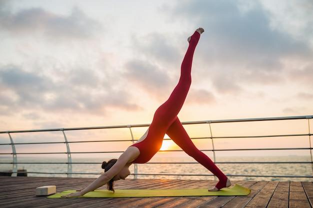 Giovane bella donna attraente esile che fa yoga di mattina su alba dal mare, stile di vita sano Foto Gratuite