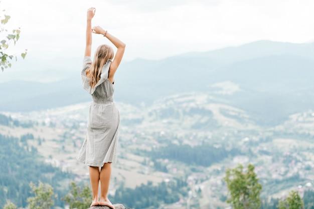 Giovane bella donna bionda a piedi nudi con i capelli lunghi in abito estivo in piedi sulla cima della montagna in pietra e godendo la vista panoramica del paesaggio favoloso con montagne e villaggio nella valle Foto Premium
