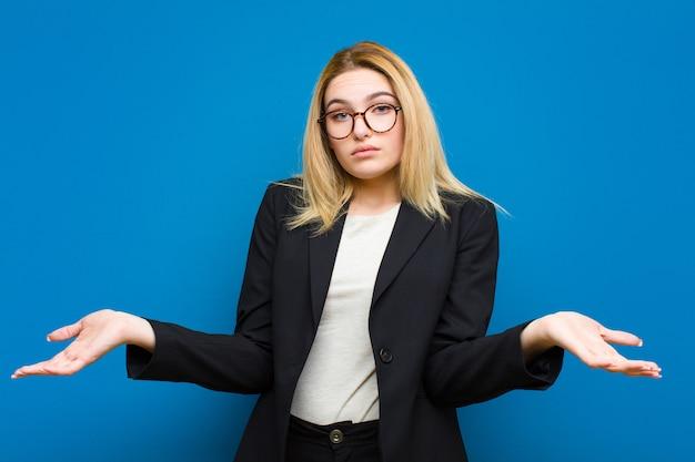 Giovane bella donna bionda che solleva il palmo alla fronte pensando oops, dopo aver fatto uno stupido errore o aver ricordato, sentendosi muta contro il piatto Foto Premium