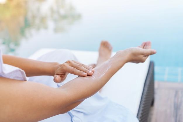 Giovane bella donna che applica protezione solare o lozione solare nel suo corpo per protezione solare della pelle alla piscina. ragazza bruna godendo le vacanze estive. Foto Premium