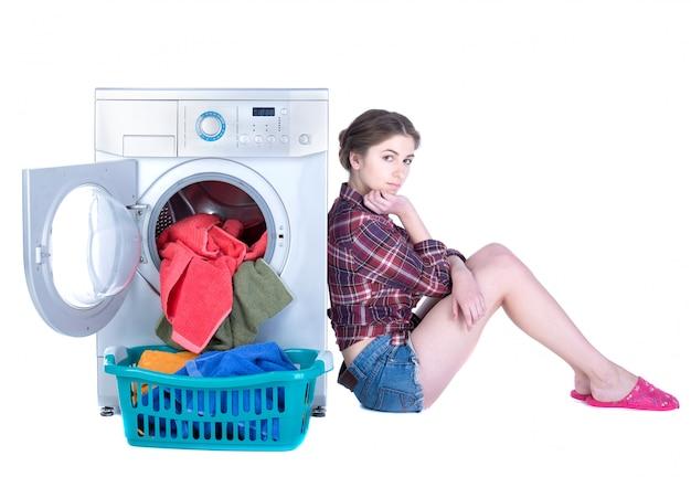 Giovane bella donna che fa lavanderia nella lavatrice. Foto Premium