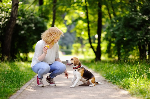 Giovane bella donna che gioca con il cane beagle nel parco estivo Foto Premium