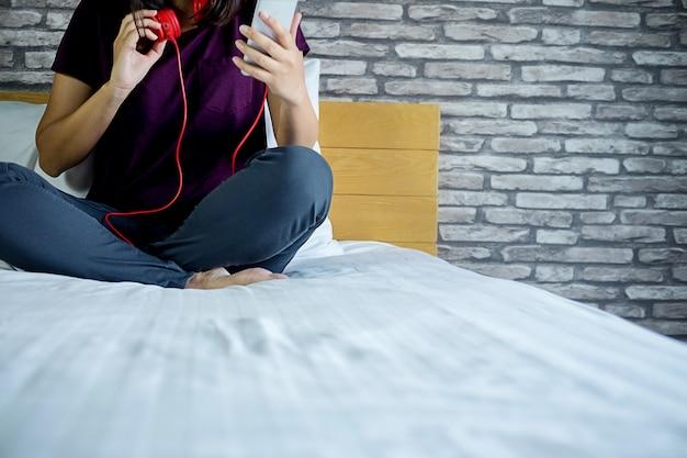 Giovane bella donna che gode della musica da tablet e rilassarsi sul ...