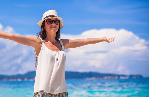 Giovane bella donna che gode della vacanza sulla spiaggia tropicale bianca Foto Premium