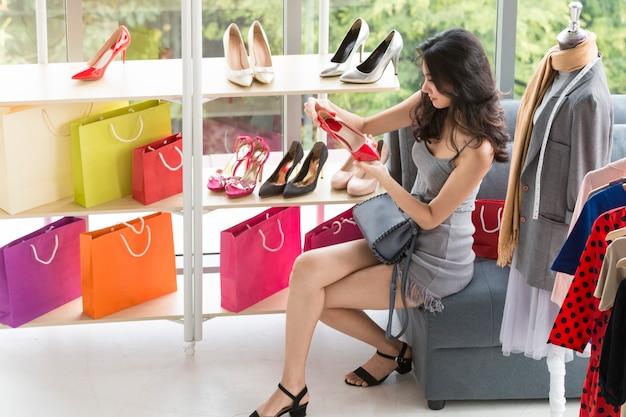 Giovane bella donna che gode nello shopping al negozio. Foto Premium