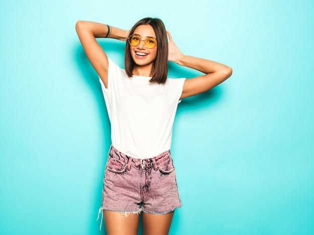 Giovane bella donna che guarda l'obbiettivo. ragazza alla moda in pantaloncini di maglietta e jeans bianchi estivi casual in occhiali da sole rotondi. la femmina positiva mostra le emozioni facciali. modello divertente isolato sul blu Foto Gratuite