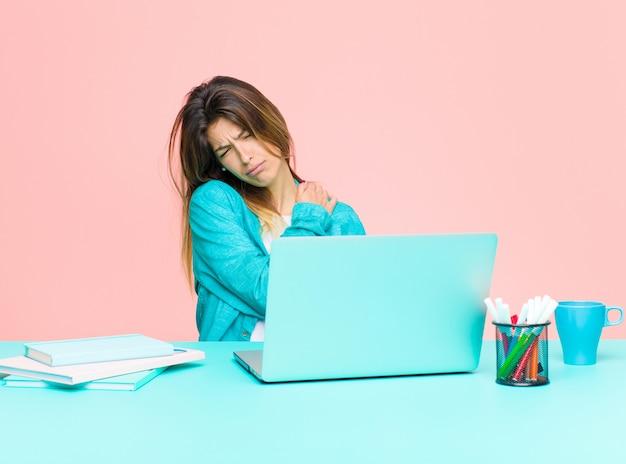 Giovane bella donna che lavora con un laptop sentendosi ansioso, malato, malato e infelice, soffrendo di dolori di stomaco o influenza Foto Premium