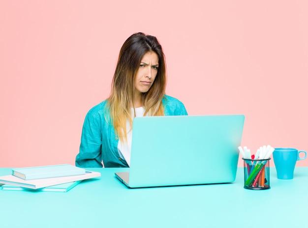 Giovane bella donna che lavora con un laptop sentendosi triste, arrabbiato o arrabbiato e guardando al lato con un atteggiamento negativo, accigliato in disaccordo Foto Premium