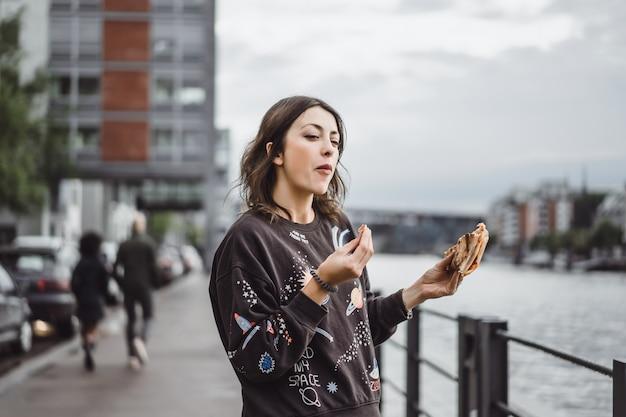 Giovane bella donna che mangia una fetta di pizza sulla via della città Foto Gratuite
