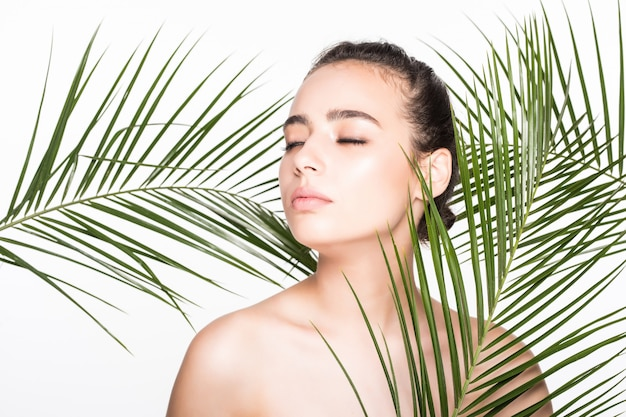 Giovane bella donna che posa con le foglie di palma verdi Foto Gratuite