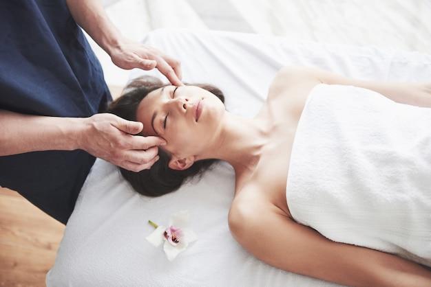 Giovane bella donna che si distende dal massaggio viso Foto Premium