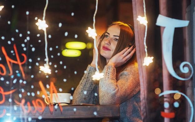 Giovane bella donna che si siede nella caffetteria, bere caffè. modella l'ascolto di musica. natale, capodanno, san valentino, vacanze invernali Foto Premium