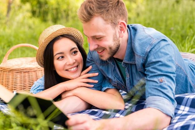 Giovane bella donna che sorride alla lettura dell'uomo in campagna Foto Gratuite