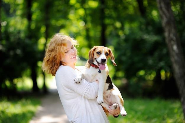 Giovane bella donna con cane beagle nel parco estivo. amorevole proprietario femminile con il suo animale domestico domestico Foto Premium
