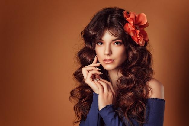 Giovane bella donna con fiori tra i capelli e il trucco, tonificante foto Foto Premium