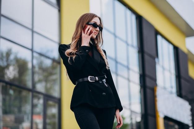 Giovane bella donna d'affari dal centro ufficio, utilizzando il telefono Foto Gratuite
