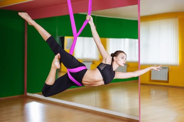 Giovane bella donna facendo pratica yoga aerea in amaca viola in palestra. Foto Premium