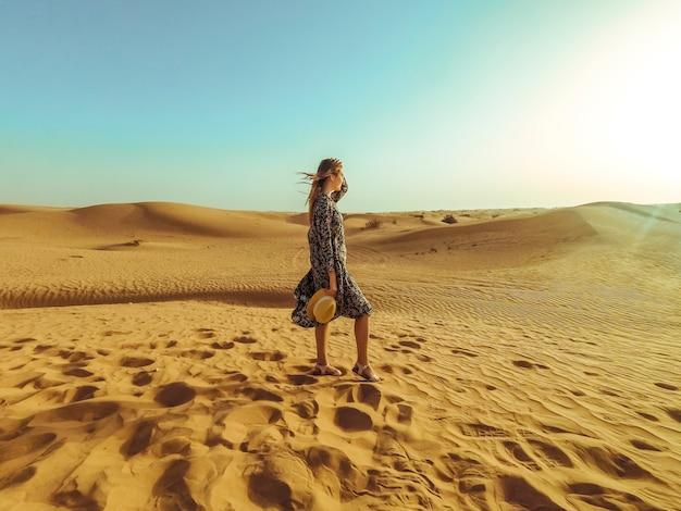 Giovane bella donna in abito lungo e con un cappello nel mezzo del deserto di dubai con la luce del sole Foto Premium