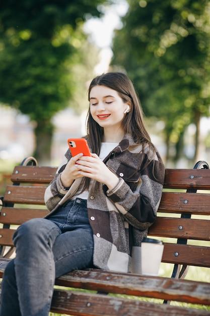 Giovane bella donna in piedi su una panchina utilizzando il computer portatile Foto Premium