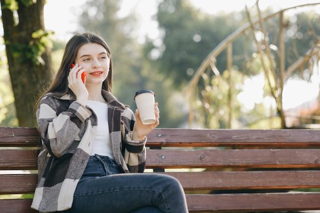 Giovane bella donna in piedi su una panchina utilizzando il telefono Foto Premium