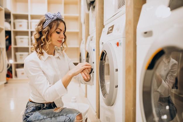 Giovane bella donna in una lavanderia a gettoni Foto Gratuite