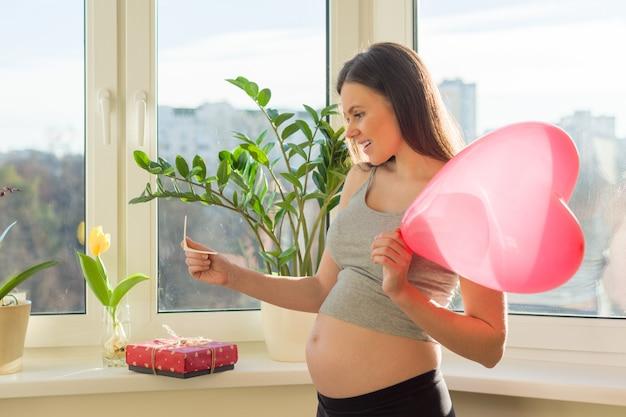 Giovane bella donna incinta con scatola regalo e palloncino cuore Foto Premium