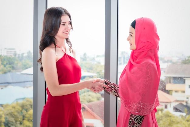 Giovane bella donna musulmana che stringe la mano con amicizie caucasiche Foto Premium