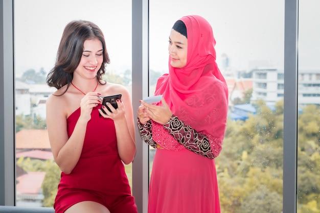 Giovane bella donna musulmana e amicizie caucasiche con telefono e carta di credito godendo nello shopping Foto Premium