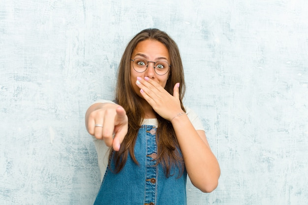 Giovane bella donna ridendo di te, indicando la fotocamera e prendendo in giro o deridendoti sopra la parete del grunge Foto Premium