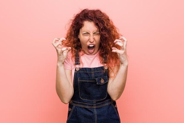 Giovane bella donna rossa di zenzero che indossa un dungaree jeans urlando di rabbia. Foto Premium