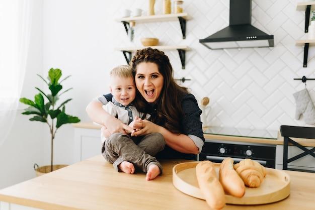 Giovane bella donna seduta al tavolo della cucina al mattino con il suo bambino piccolo Foto Premium