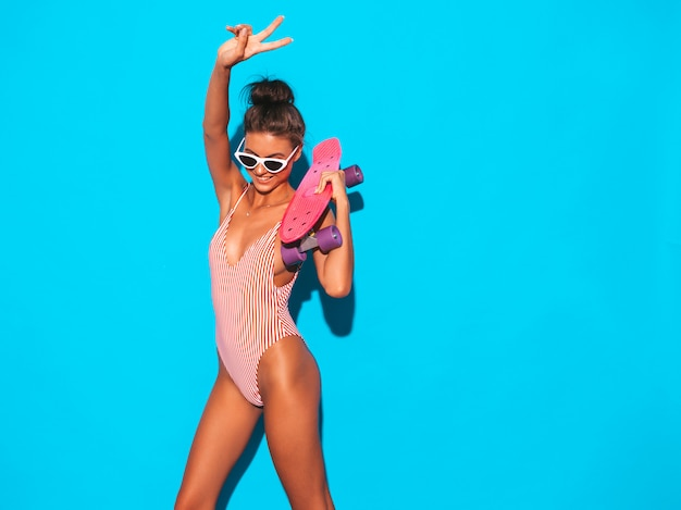 Giovane bella donna sorridente sexy dei pantaloni a vita bassa in occhiali da sole ragazza alla moda in costume da bagno dello swimwear di estate. femmina positiva che impazzisce con il pattino rosa del penny, isolato sul blu. Foto Gratuite