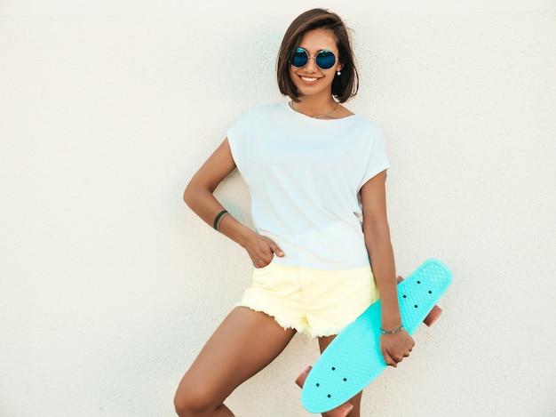 Giovane bella donna sorridente sexy dei pantaloni a vita bassa in occhiali da sole. ragazza alla moda in maglietta e shorts di estate. femmina positiva con il pattino blu del penny che posa nella via vicino al muro bianco Foto Gratuite