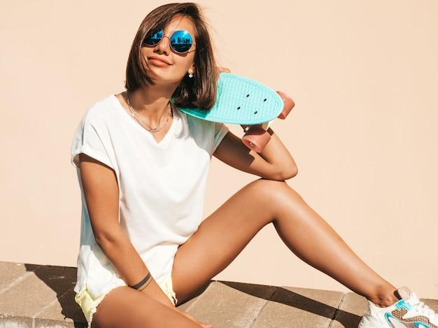 Giovane bella donna sorridente sexy dei pantaloni a vita bassa in occhiali da sole ragazza alla moda in maglietta e shorts di estate femmina positiva con il pattino blu del penny che posa sui precedenti della via Foto Gratuite