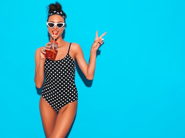 Giovane bella donna sorridente sexy dei pantaloni a vita bassa in occhiali da sole ragazza in costume da bagno dello swimwear dei piselli estivi. posando vicino alla parete blu, bevendo bevanda smoozy fresca del cocktail. mostra il segno di pace Foto Gratuite