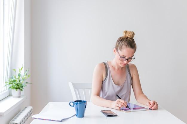 Giovane bella donna utilizzando stilo sulla tavoletta digitale grafica Foto Gratuite