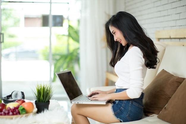 Giovane bella donna utilizzando un computer portatile a casa. Foto Gratuite